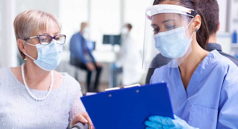 Emergency Physicians Wearing Mask While Working With Patient